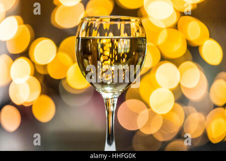 A glass of Pinot Grigio white wine with sparkling lights in the background - Stock Photo