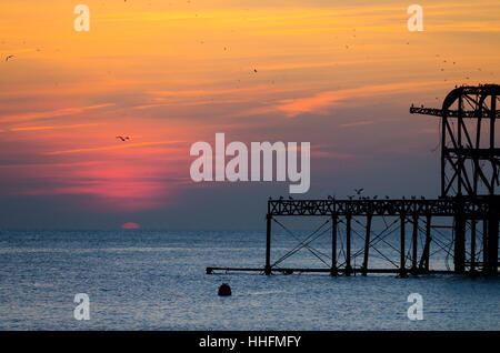Brighton, UK. 18th January, 2017. A mild sunny winter afternoon brings people to the seafront to watch starling - Stock Photo