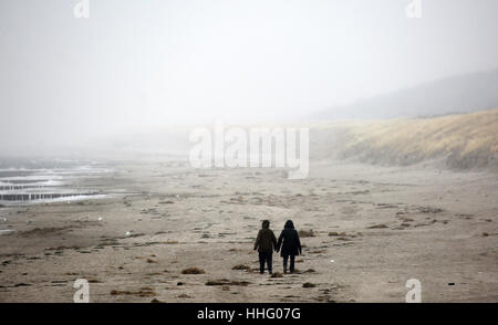 Graal-Mueritz, Germany. 19th Jan, 2017. Two people walk along the Baltic Sea beach during dull weather in Graal - Stock Photo