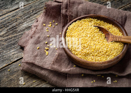 Uncooked bulgur in wooden bowl on wooden table background, rustic style. Bulgur wheat grains - Stock Photo