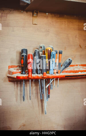 several screwdrivers hanging on wooden wall at workshop - Stock Photo