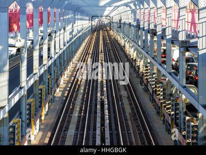 View of empty subway tracks at rush hour across the Williamsburg Bridge between Brooklyn and Manhattan in New York - Stock Photo