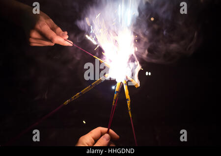 Close-up of hands coming together to ignite sparklers (fireworks) during an evening celebration. - Stock Photo