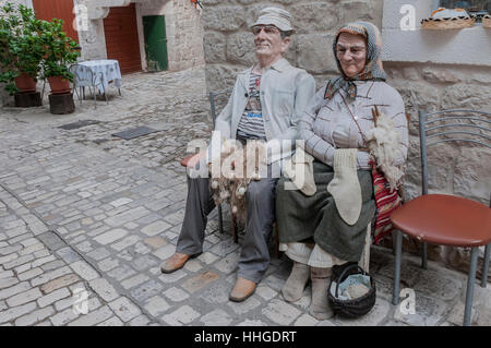 Life-sized dolls of a fisherman and his wife, who is knitting, outside of a tourist shop in Trogir, Croatia's Old - Stock Photo