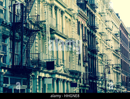 New York City view of exterior facade on ornate old apartment building residence with fire escapes seen from lower - Stock Photo