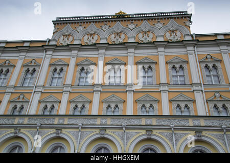 Exterior of yellow and white building in the Kremlin in Moscow Russia. Photographed from below with light blue sky - Stock Photo