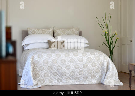 Bed in bedroom setting with luxury bedspread - Stock Photo