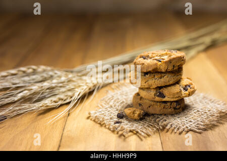 Chocolate cookies on a cloth sack on wood. Chocolate chip cookies and rice malt shot on a brown cloth . - Stock Photo