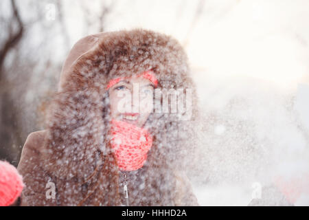 Lovely teen girl in pink knitted gloves, hat and scarf, fur hooded jacket winter walks in the park. She throws snow - Stock Photo