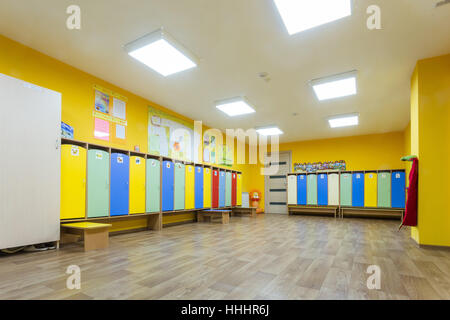 Yellow colored changing room and lockers of kindergarten for children - Stock Photo