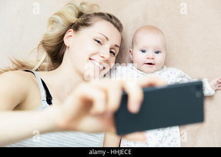 mother and little infant baby taking selfie with phone in bed - Stock Photo
