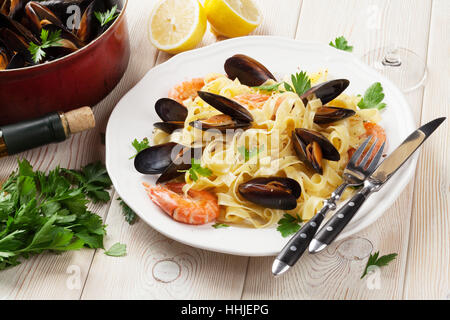 Pasta with seafood and white wine on wooden table. Mussels and prawns