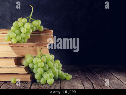 White grapes over old books on table in front of stone wall with copy space. Toned - Stock Photo