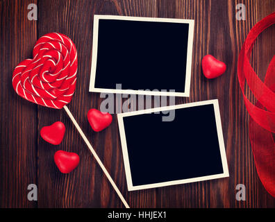 valentines day photo frames and candy hearts over wooden table top view with copy space