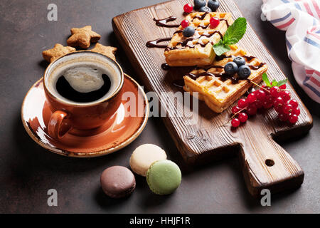 Coffee, sweets and waffles with berries on cutting board - Stock Photo