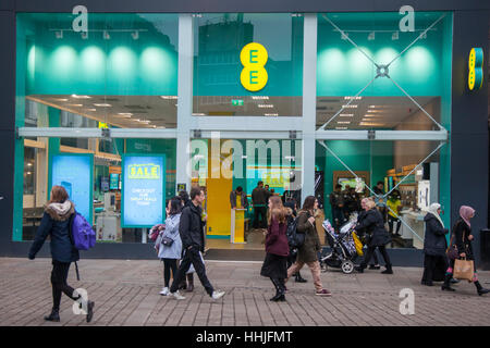 People passing EE Mobile Phone shop in a busy, crowded, Piccadilly, Manchester city centre, UK - Stock Photo