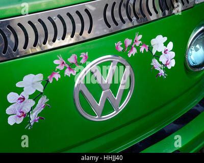 VW Volkswagen green Campervan close-up with personalised floral additions surrounding VW logo - Stock Photo