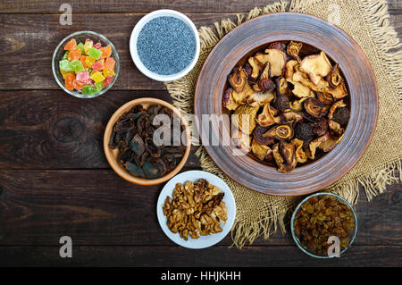 Dried fruit (apples, pears, apricot), berries, walnut kernels, raisins, poppy seeds in a bowl on dark wooden background. - Stock Photo