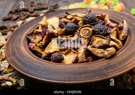 Dried fruit (apples, pears, apricots), berries, raisins and nuts in a bowl on dark wooden background. Close up. - Stock Photo