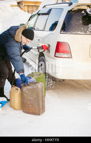 adult man fills a car with petrol at a fuel station in the winter. refueling nozzle man holding in his hand, pouring - Stock Photo