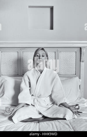 Blonde woman in meditative yoga position - Stock Photo