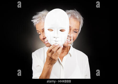 older woman hiding happy and sad face behind mask - Stock Photo