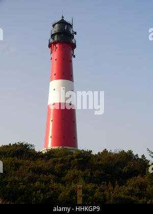 a red and white lighthouse in Northern Germany at evening time - Stock Photo