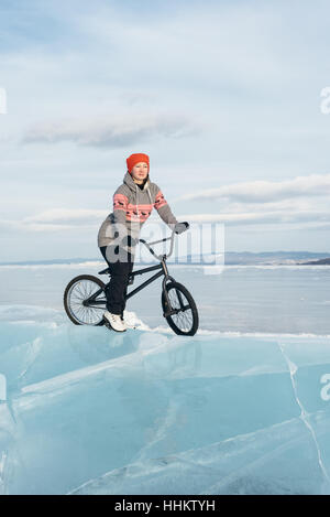 Girl standing on a bmx on the beautiful and dangerous ice. - Stock Photo