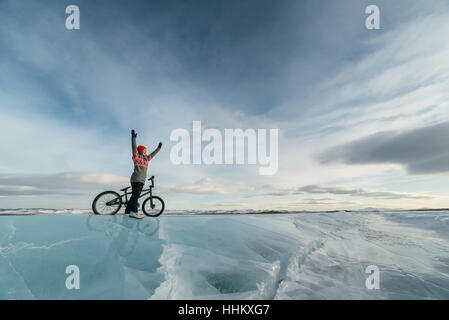 Girl standing on a bmx on the beautiful and dangerous ice and enjoys success. - Stock Photo