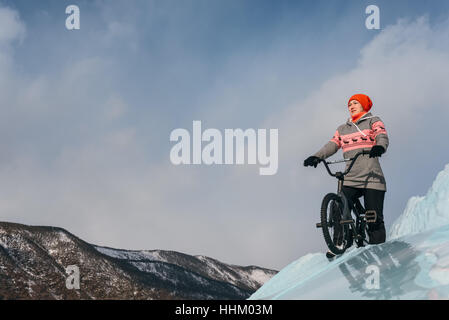 Girl standing on a bmx on the beautiful and dangerous ice. Ice the deepest lake in the world. This is Lake Baikal. - Stock Photo