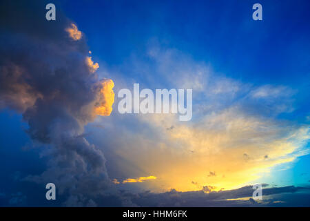 Dramatic sunset sky with yellow, blue and orange approaching thunderstorm clouds. - Stock Photo