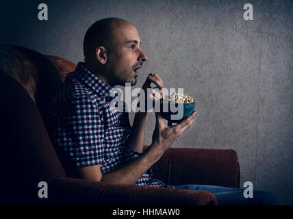 man sits in a chair and watching TV at night at home - Stock Photo