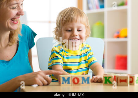 Mother teaches son child to read letters and words playing with cubes Stock Photo
