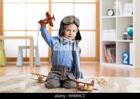 Child pretending to be aviator. Kid playing with toy airplanes at home - Stock Photo