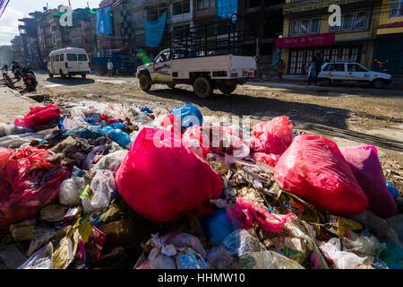 Garbage piled up beside busy road in Bouda suburb, Kathmandu, Nepal - Stock Photo
