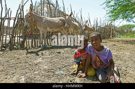 Boys and donkeys in front of mud hut, Orma ethnic community, Marafa, Tana River Delta, Kenya - Stock Photo