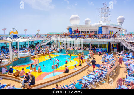 Passengers aboard Royal Caribbean's Brillance of the Seas relaxing by the pool during a day at sea. - Stock Photo