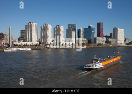 Skyline with skyscrapers on Boompjeskai, cargo ship on the Nieuwe Maas River, Rotterdam, Holland, Netherlands - Stock Photo