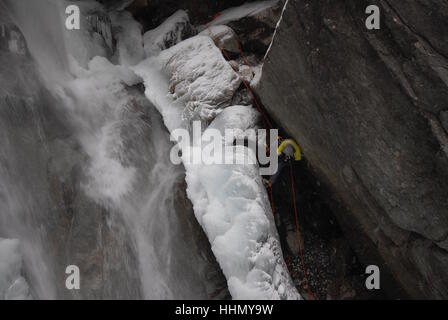 Photographer suspended on fixed ropes securing himself in place in order to photograph ice climbers on partially - Stock Photo