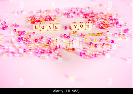 Love you text with multicolor beads with pinkish ambient. - Stock Photo