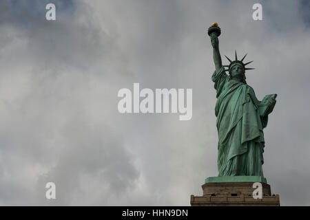 The Statue of Liberty in front of overcast sky. Liberty Island, New York Harbor, New York City, United States of - Stock Photo