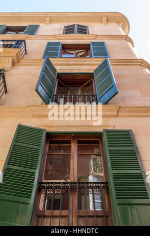 Majorcan Spanish style with windows and green shutter doors with wrought iron railings - Stock Photo