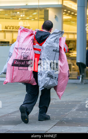 Postman carrying several royal mail parcel bags, UK - Stock Photo