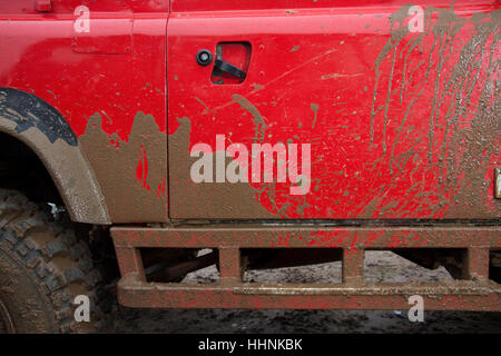 Mud splashes on the side of a bright red Land Rover - Stock Photo