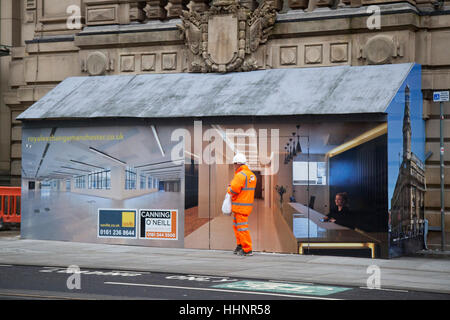 Workman in hi-vis clothing walking past an interior office scene painted on Innovative Hoarding, A unusual building - Stock Photo