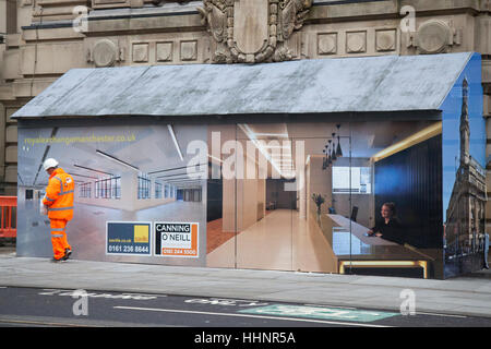 Workman in hi-vis clothing walking past an interior office scene painted on Innovative Hoarding, painted timber - Stock Photo