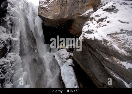 Photographer securing himself in place next to ice climbing route on partially frozen waterfall preparing to photograph - Stock Photo