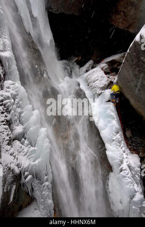 Photographer suspended from fixed climbing ropes on edge of partially frozen waterfall securing himself in place - Stock Photo