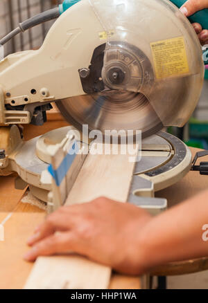 carpenter's hands on wood at table saw making a cut - Stock Photo