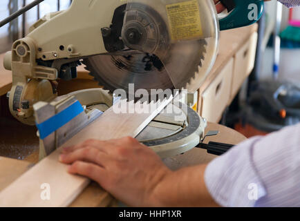 carpenter's hands on wood at table saw - Stock Photo